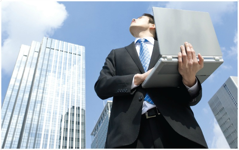 Image of a man looking at the clouds while working on his computer