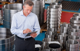 Businessman using digital tablet among steel roller bearings in manufacturing plant